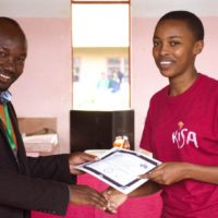 A Kisa Scholar receives her participation certificate for her EYOP.